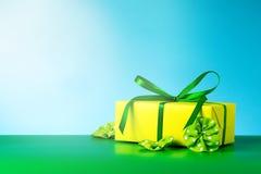 Fondo verde blu di regalo del contenitore dell'arco giallo del raso Immagini Stock Libere da Diritti