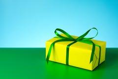 Fondo verde blu di regalo del contenitore dell'arco giallo del raso Fotografie Stock Libere da Diritti