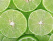 Fondo verde con gli agrumi delle fette della calce fotografie stock libere da diritti