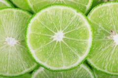 Fondo verde con gli agrumi delle fette della calce immagine stock