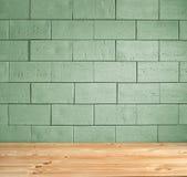 Fondo verde del ladrillo y piso de madera foto de archivo