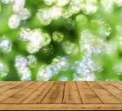 Fondo verde della luce dell'estratto del bokeh, molto bokeh della foresta con la tavola di legno Immagini Stock Libere da Diritti