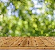 Fondo verde della luce dell'estratto del bokeh, molto bokeh della foresta con la tavola di legno Fotografia Stock Libera da Diritti