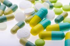 Fondo verde delle pillole sul bianco Fotografie Stock