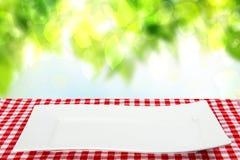 Fondo vuoto del piatto Piatto bianco vuoto sulla tavola con il tovagliolo rosso o tovaglia sopra il fondo naturale astratto di es immagini stock libere da diritti