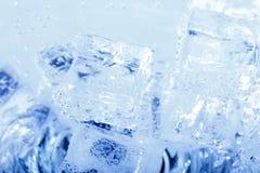 Fondos con los cubos de hielo en agua chispeante Fotos de archivo libres de regalías