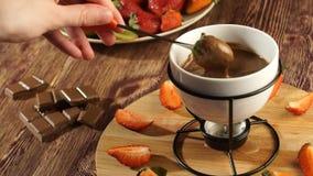 fondue το κορίτσι παίρνει τις κόκκινες φράουλες σε ένα δίκρανο dunks στην καυτή σοκολάτα από fondue απόθεμα βίντεο