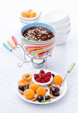 Fondue chocolate with almond. And fruits Royalty Free Stock Photos