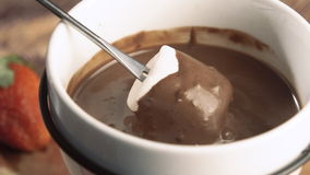 Fondue Close-up marshmallow being dipped in chocolate stock video footage