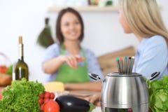 Fondue dans un pot au fond des amis faisant cuire ensemble, plan rapproché Intérieurs et cookware de cuisine Photo stock