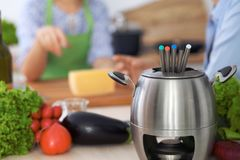 Fondue dans un pot au fond des amis faisant cuire ensemble, plan rapproché Intérieurs et cookware de cuisine Photographie stock libre de droits