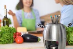 Fondue dans un pot au fond des amis faisant cuire ensemble, plan rapproché Intérieurs et cookware de cuisine Images libres de droits