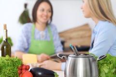 Fondue dans un pot au fond des amis faisant cuire ensemble, plan rapproché Intérieurs et cookware de cuisine Photos libres de droits