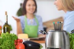 Fondue dans un pot au fond des amis faisant cuire ensemble, plan rapproché Intérieurs et cookware de cuisine Image stock