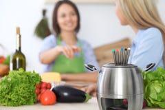 Fondue dans un pot au fond des amis faisant cuire ensemble, plan rapproché Intérieurs et cookware de cuisine Images stock