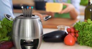 Fondue dans un pot au fond des amis faisant cuire ensemble, plan rapproché Intérieurs et cookware de cuisine Photographie stock