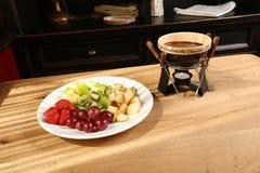 Fondue de chocolat avec l'assortiment de fruits sur le fond en bois Images libres de droits