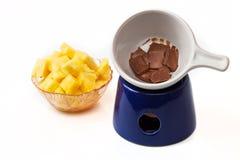 'fondue' de chocolate con los pedazos de la piña Imagen de archivo libre de regalías