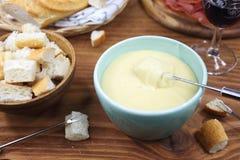 'fondue' de queso tradicional con el baguette y la copa Imágenes de archivo libres de regalías