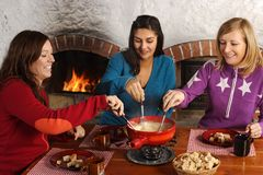 Fondue dinner with friends. Photo of three beautiful females dipping bread into the melted cheese in a fondue pot stock image