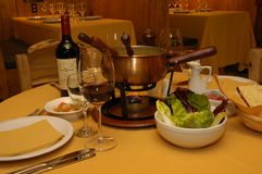 Fondue. Dinning table with fondue and wine Stock Photos