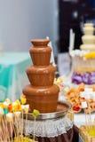 Fondue fountain of dark chocolate being dipped Stock Photo