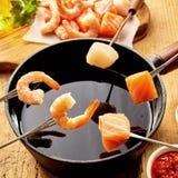 Fondue gastronome de fruits de mer avec des crevettes roses et des saumons Photo libre de droits
