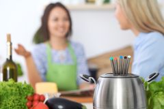 Fondue in a pot at the background of friends cooking together, close-up. Kitchen interiors and cookware stock photography