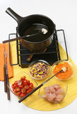 Fondue snack. Delicious meat fondue with salad and vegetables royalty free stock image