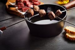 Fonduegafflar av lagat mat nötkött med krukan av varm olja Royaltyfri Fotografi