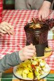 Fonduepartei der süßen Schokolade des Nachtischs mit Würfeln von Äpfeln, von Birnen, von Ananas und von Trauben Stockfoto