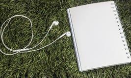 Fone de ouvido e caderno colocados na grama verde imagem de stock royalty free