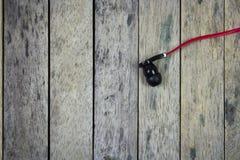 Fone de ouvido posto sobre a prancha de madeira Imagem de Stock