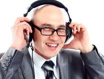 Fone de ouvido vestindo do homem de negócios que esforça-se para ouvir-se imagem de stock royalty free