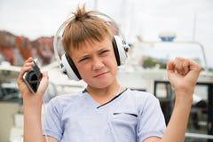 Fones de ouvido à moda do menino que escutam a música Foto de Stock Royalty Free