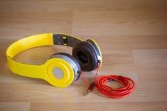 Fones de ouvido amarelo com 3 5 milímetros jaque estereofônico no fundo de madeira Imagem de Stock