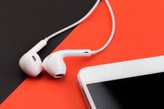 Fones de ouvido brancos com o telefone no fundo preto e vermelho imagem de stock royalty free