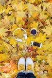 Fones de ouvido brancos com um jogador e um copo do chá e do café em um fundo das folhas amarelas Fotos de Stock Royalty Free