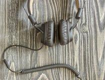 Fones de ouvido com o cabo que encontra-se no fundo de madeira Foto de Stock
