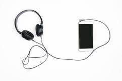 Fones de ouvido com smartphone em um fundo branco Imagem de Stock Royalty Free