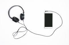 Fones de ouvido com smartphone em um fundo branco Foto de Stock