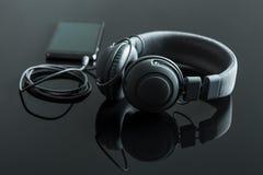 Fones de ouvido conectados ao telefone celular imagens de stock royalty free