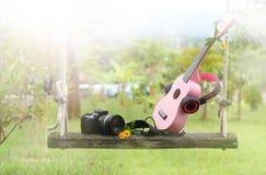 Fones de ouvido cor-de-rosa doces, música da uquelele, câmera no balanço de madeira Imagem de Stock Royalty Free