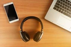 Fones de ouvido da Sobre-orelha e telefone esperto com o portátil no assoalho de madeira, dispositivos usados da eletrônica foto de stock