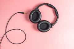 Fones de ouvido desconectado preto do estúdio no rosa Imagens de Stock Royalty Free