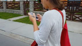 Fones de ouvido do estudante fêmea que olham no app do smartphone, rua de passeio, perigo da vida vídeos de arquivo