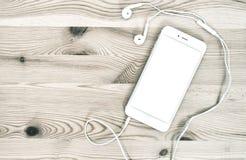 Fones de ouvido do telefone de Digitas no fundo de madeira Fotografia de Stock