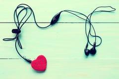 Fones de ouvido e coração no fundo de madeira fotos de stock royalty free