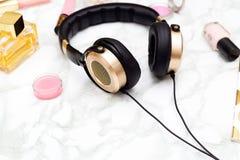 Fones de ouvido e cosméticos dourados em um fundo de mármore feminine foto de stock