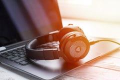 Fones de ouvido e laptop pretos imagem de stock royalty free